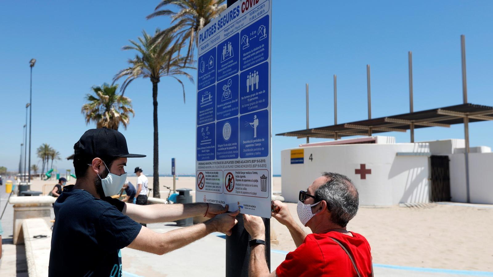 Dos operaris col·loquen un cartell a la platja de la Malva-rosa per senyalitzar els protocols sanitaris per la COVID-19