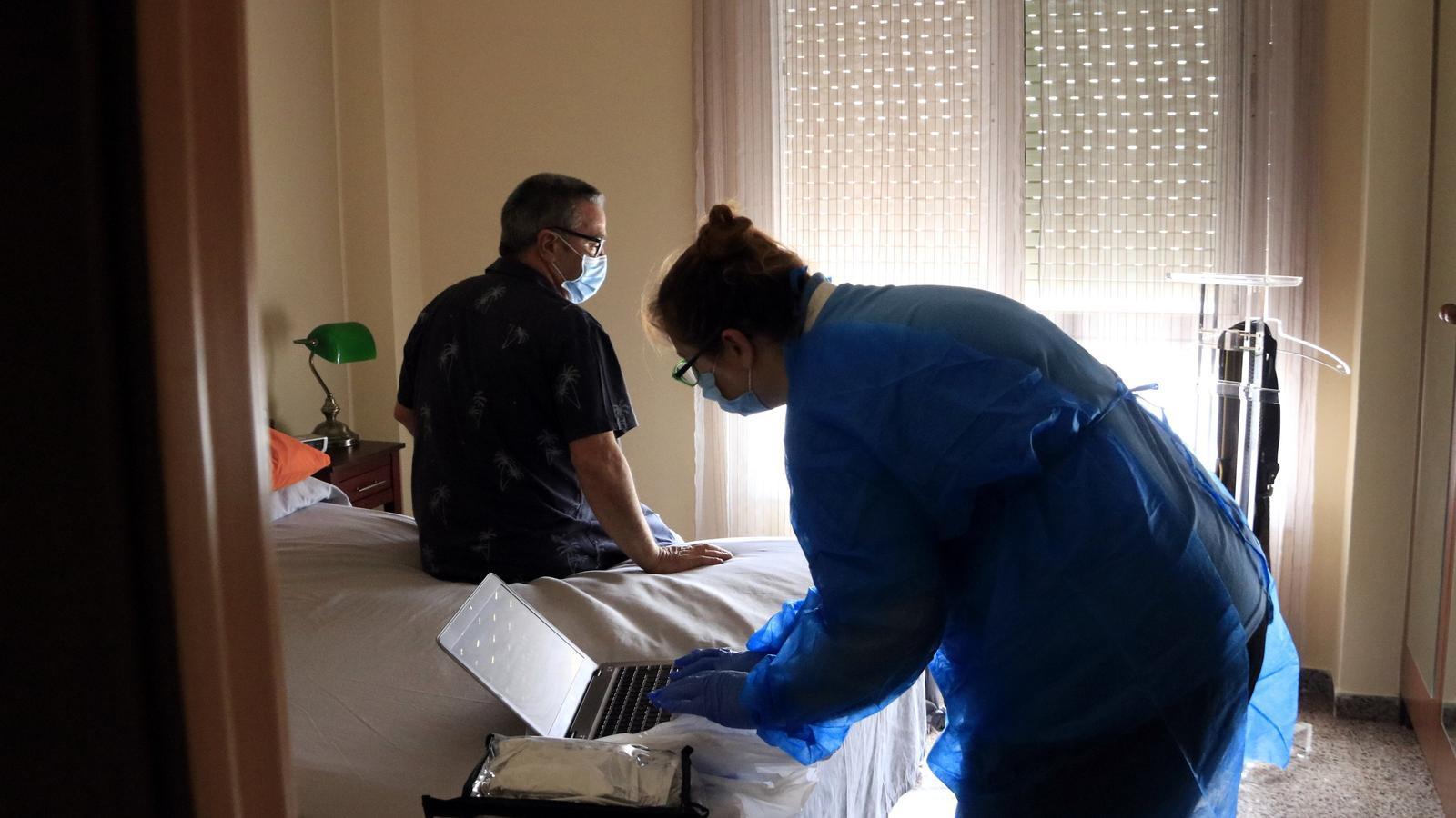 Begoña Ibáñez, infermera del dispositiu d'Hospitalització a Domicili de l'Hospital Clínic, prepara l'ordinador per fer un electrocardiograma a Óscar Villalvilla, pacient amb una insuficiència cardíaca, a l'habitació de casa seva