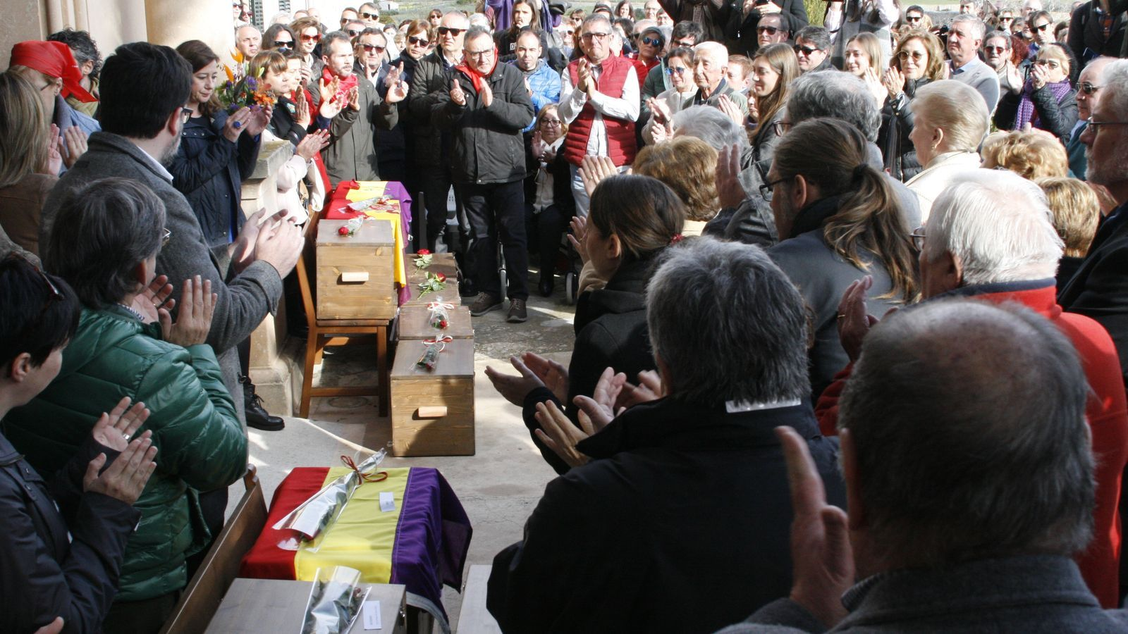 Els petits fèretres amb les restes, exposats davant el cementeri, enmig de l'esclat d'aplaudiments d'una multitud que ha assistit a l'acte.