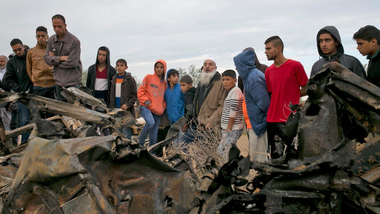 Un grup de palestins al costat d'un cotxe destruït per l'atac aeri ahir de l'exèrcit israelià