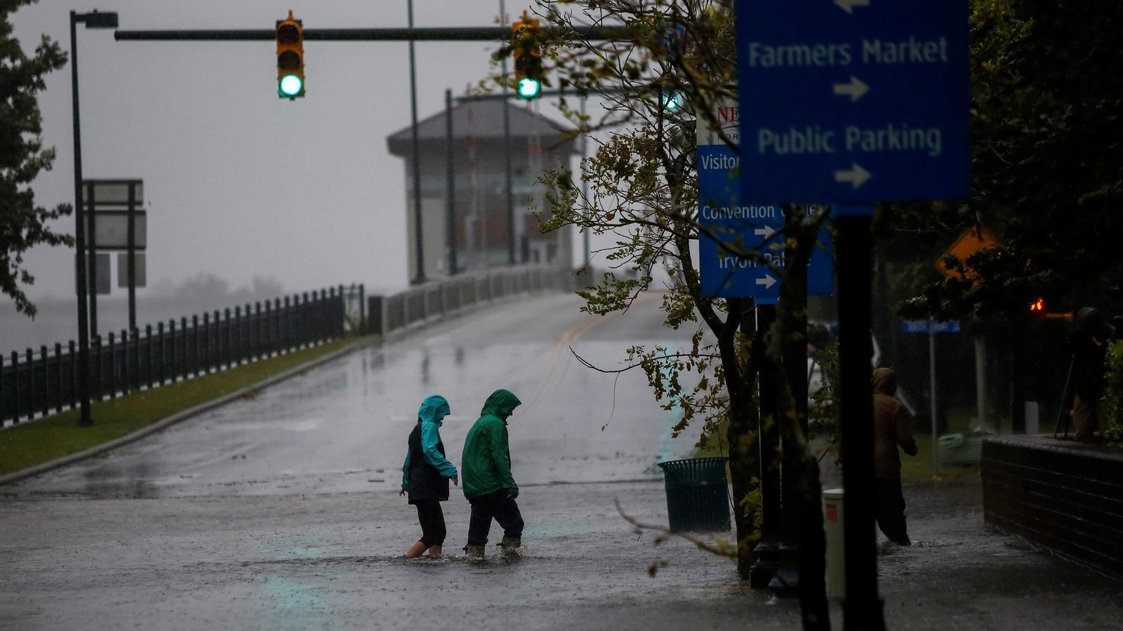 Una parella creua un carrer inundat hores abans de l'arribada del 'Florence', a New Bern, Carolina del Nord