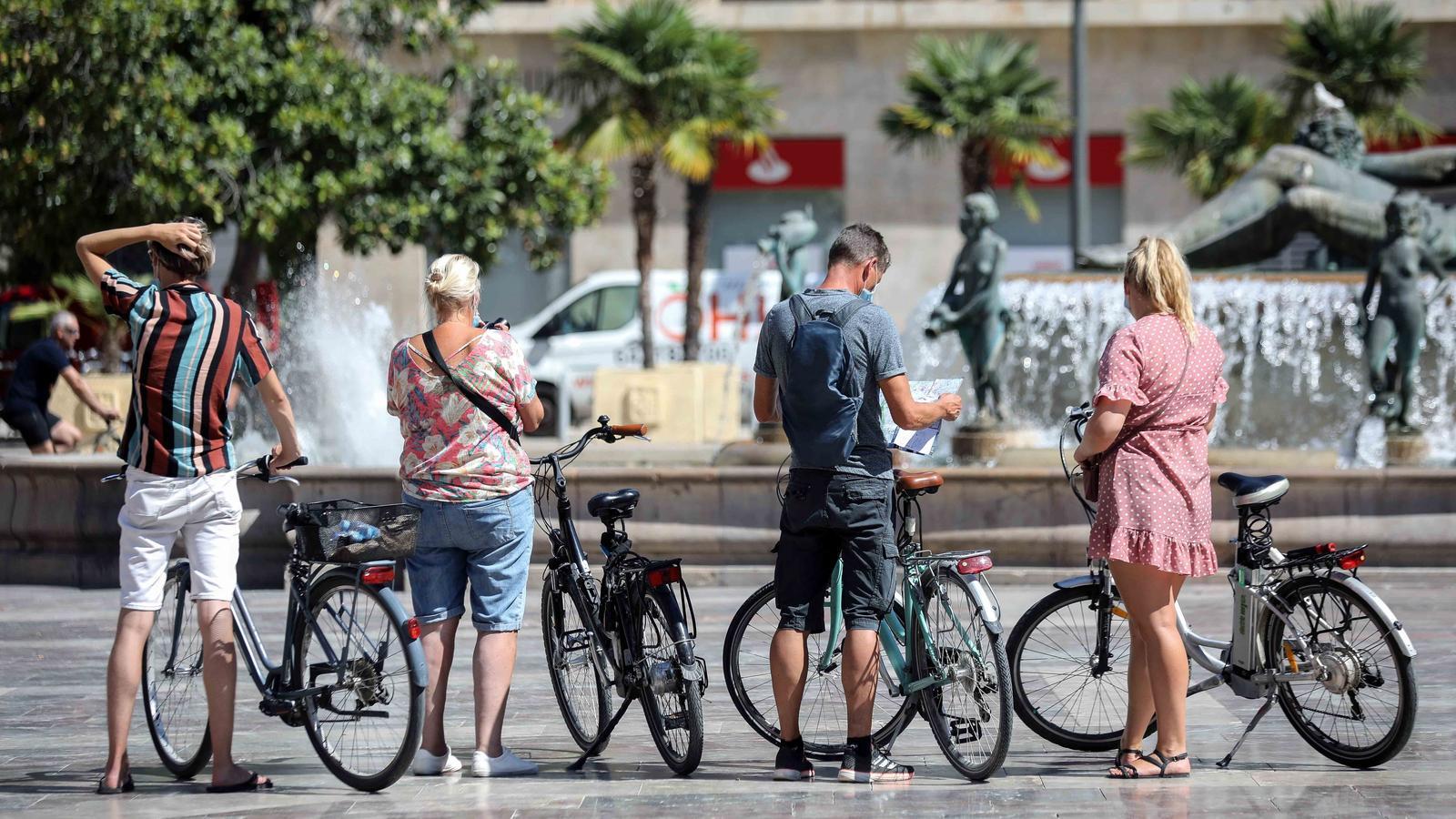 Un grup de turistes visiten amb bicicleta el centre de València