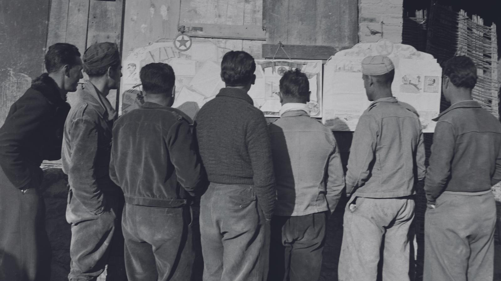 Un grup de soldats llegint un periòdic mural