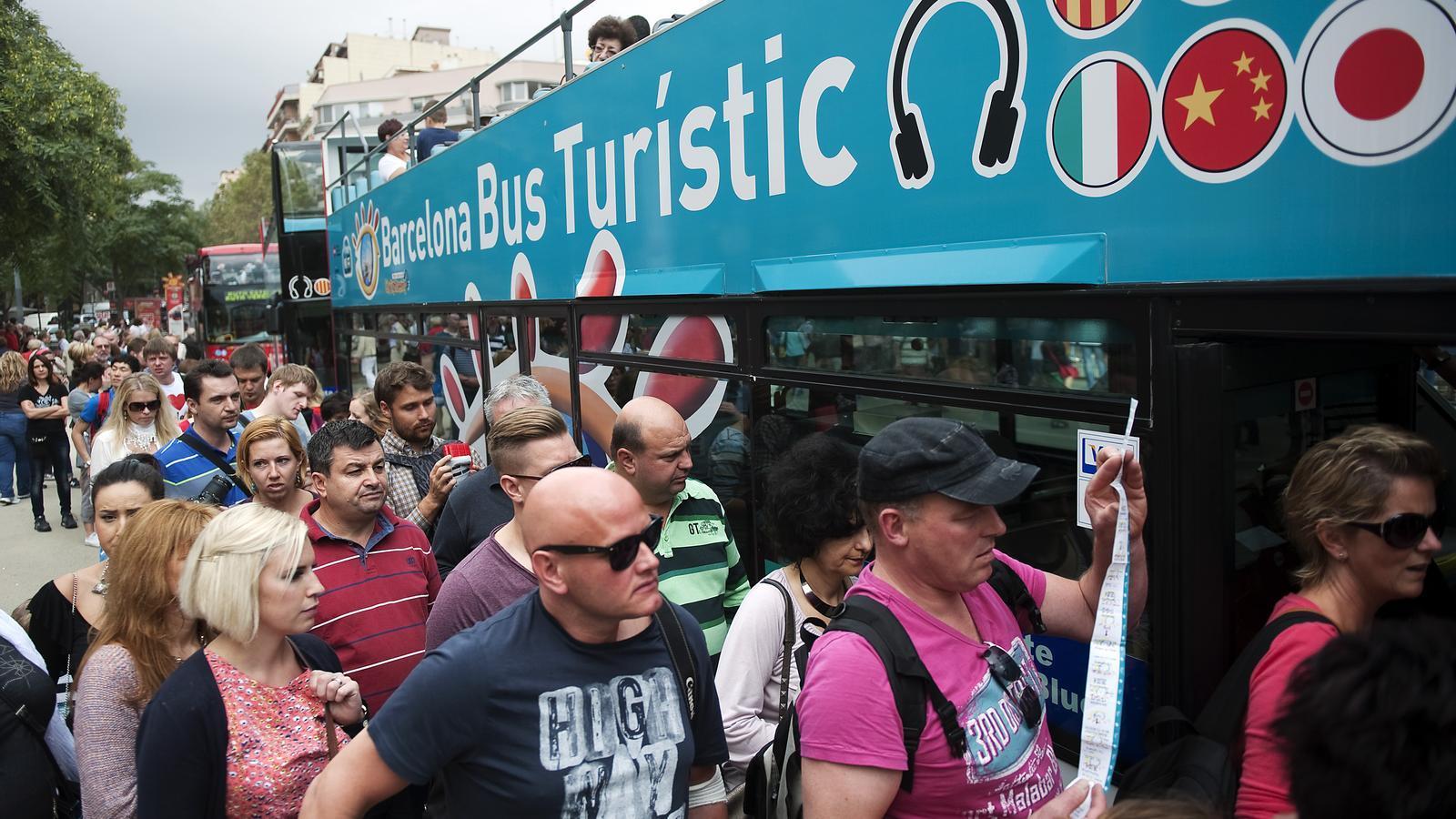 Un grup de turistes esperen per pujar al bus turístic / FRANCESC MELCION