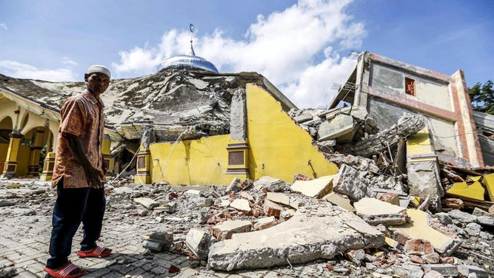 Un home passa per davant d'una mesquita destruïda per la sacsejada.