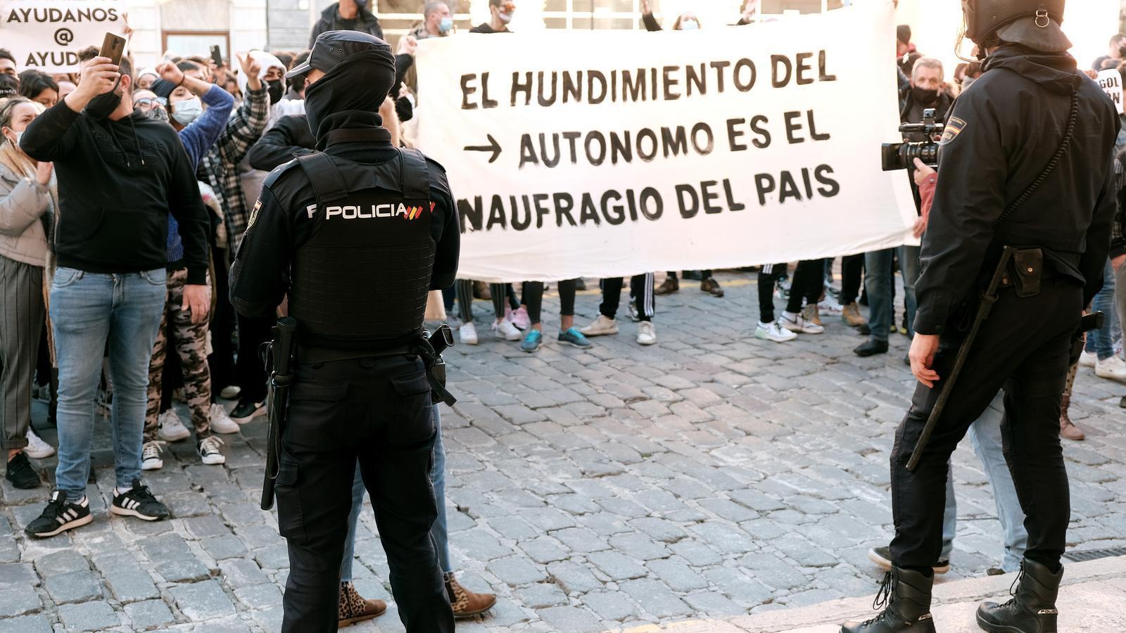 Els manifestats aguanten un cartell davant de la Policia Nacional durant la manifestació.