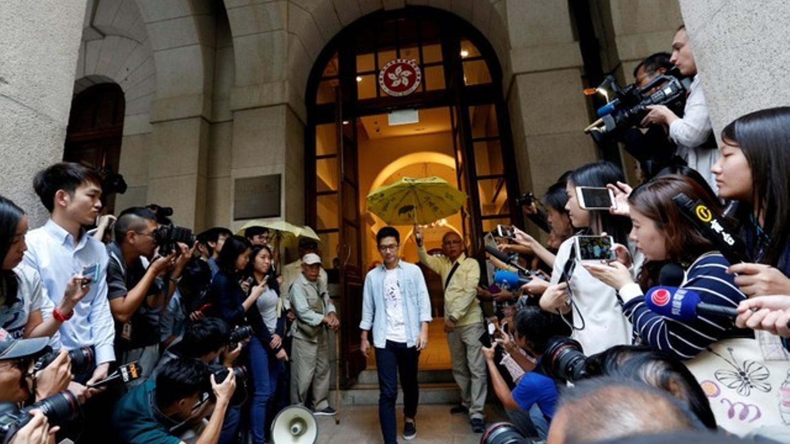 Nathan Law surt del tribunal sota un dels característics paraigües groc del moviment pro-democràtic.