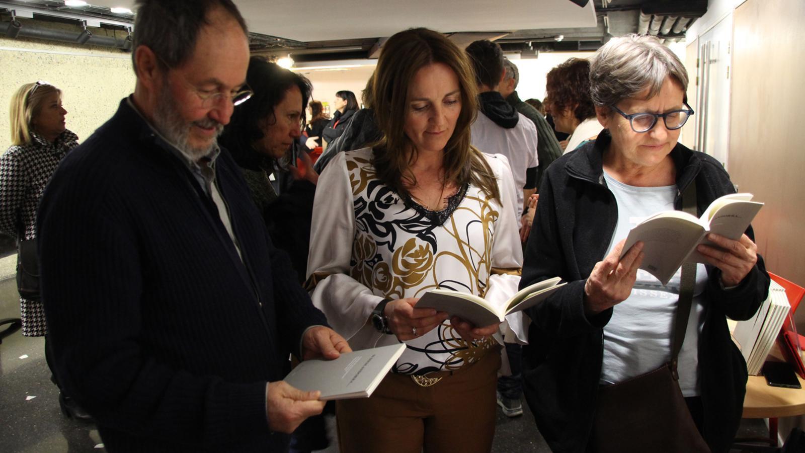 La ministra Olga Gelabert i els responsables de l'Editorial Andorra, fullejant l'antologia. / M. T. (ANA)