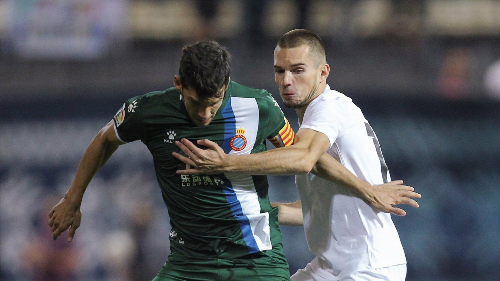 El capità de l'Espanyol, Javi López, conduint la pilota davant la pressió del futbolista del Zoryà Bogdan Mikhailitxenko.