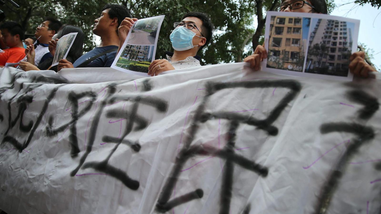 Afectats per les explosions de Tianjin, a la Xina, protesten i reclamen ajut mostrant imatges de les cases destrossades / EFE / EPA