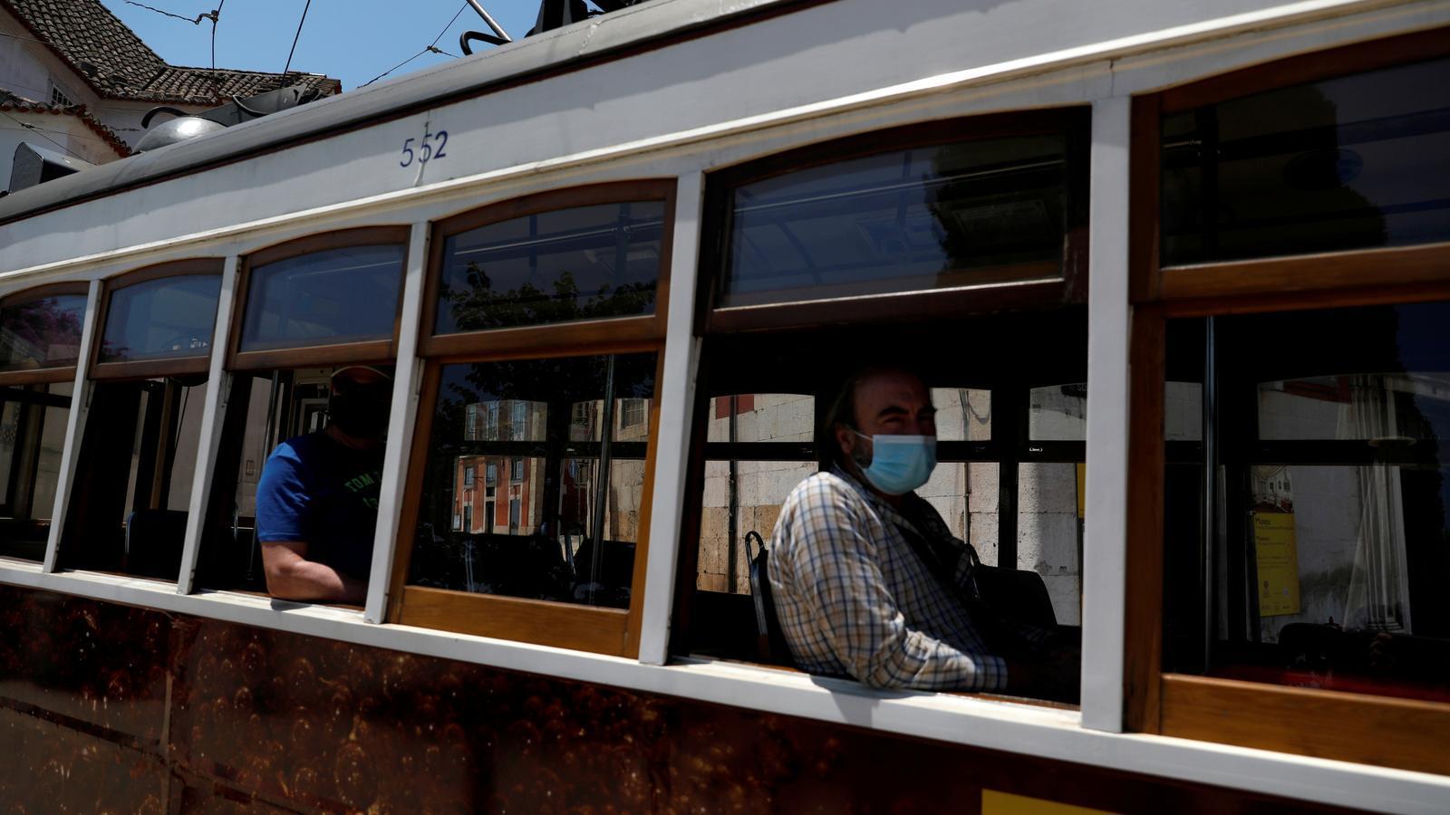 Dos passatgers amb mascareta viatjant en el tramvia de Lisboa