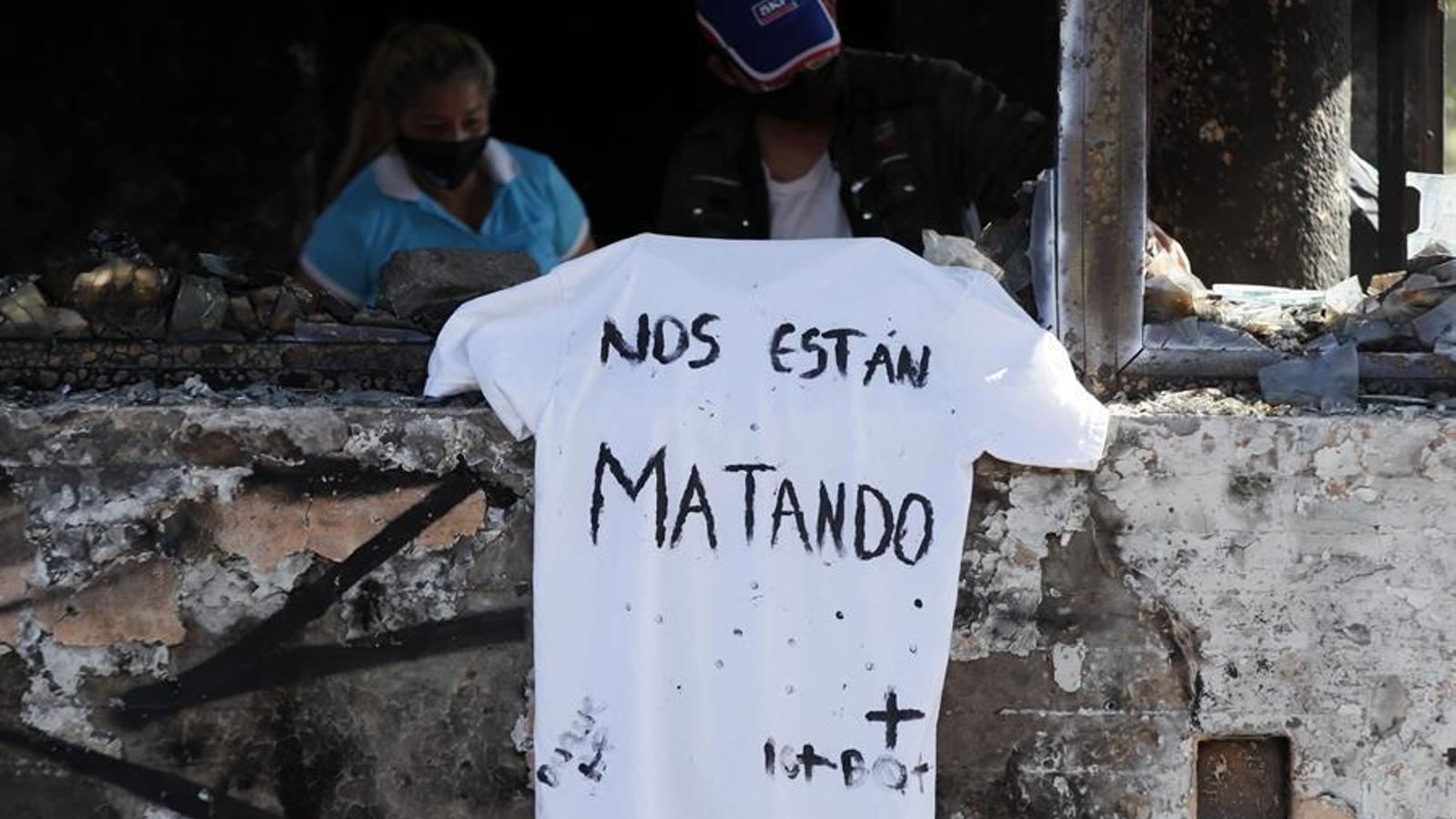 """Una samarreta amb el missatge """"Ens estan matant"""" penja sobre les restes d'un CAP incendiat a Bogotà, després d'una nit de protestes per l'assassinat de l'advocat Javier Ordóñez a mans de la policia"""
