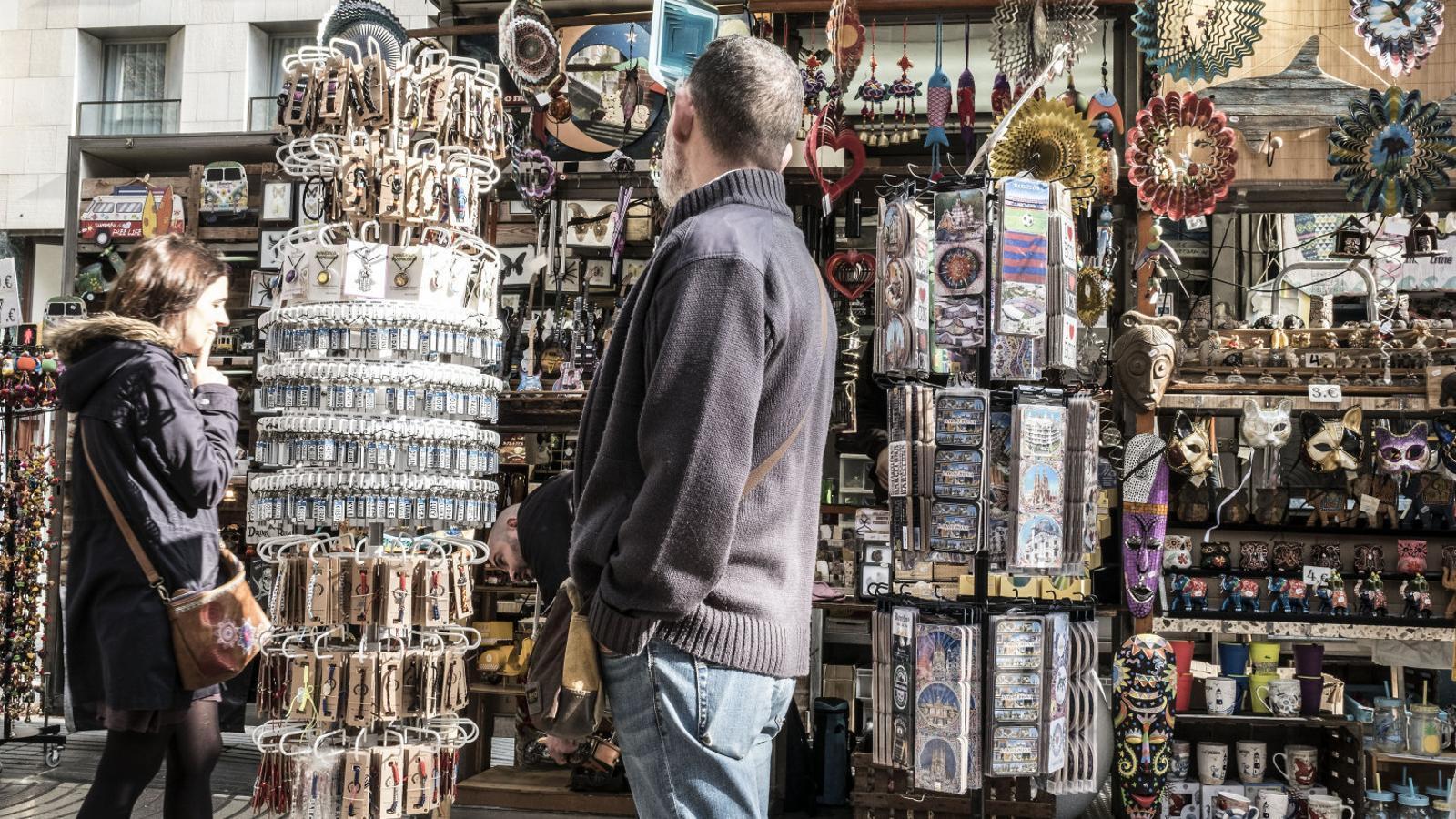 Uns clients  comprant souvenirs en una de les parades ubicades a la part central de la Rambla.