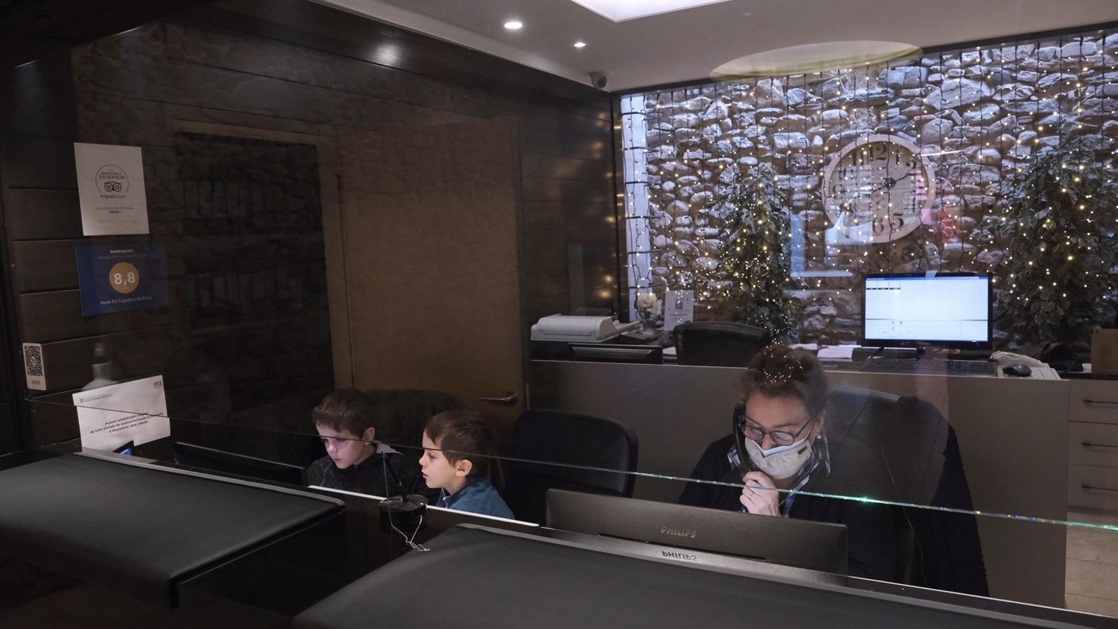 Els nens jugant a l'ordinador de la recepció mentre no paren d'arribar cancel·lacions de reserves