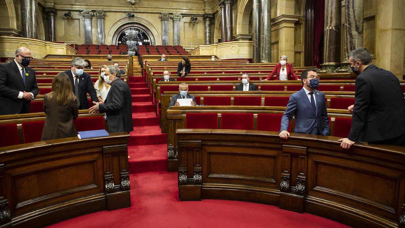 El president Torra, a la dreta, parlant amb membres del grup parlamentari de JxCat i el vicepresident Pere Aragonès, a l'altra banda de l'hemicicle, abans de l'inici del debat de política general que ha tingut lloc aquesta setmana.