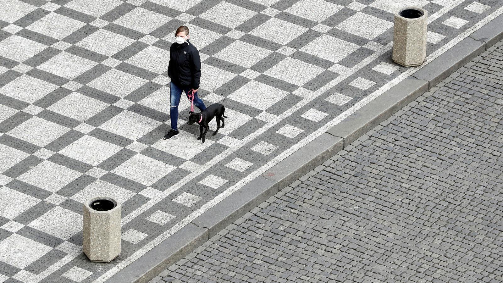 Una dona passeja el gos per Praga, amb una mascareta que és. obligatòria per a sortir al carrer.