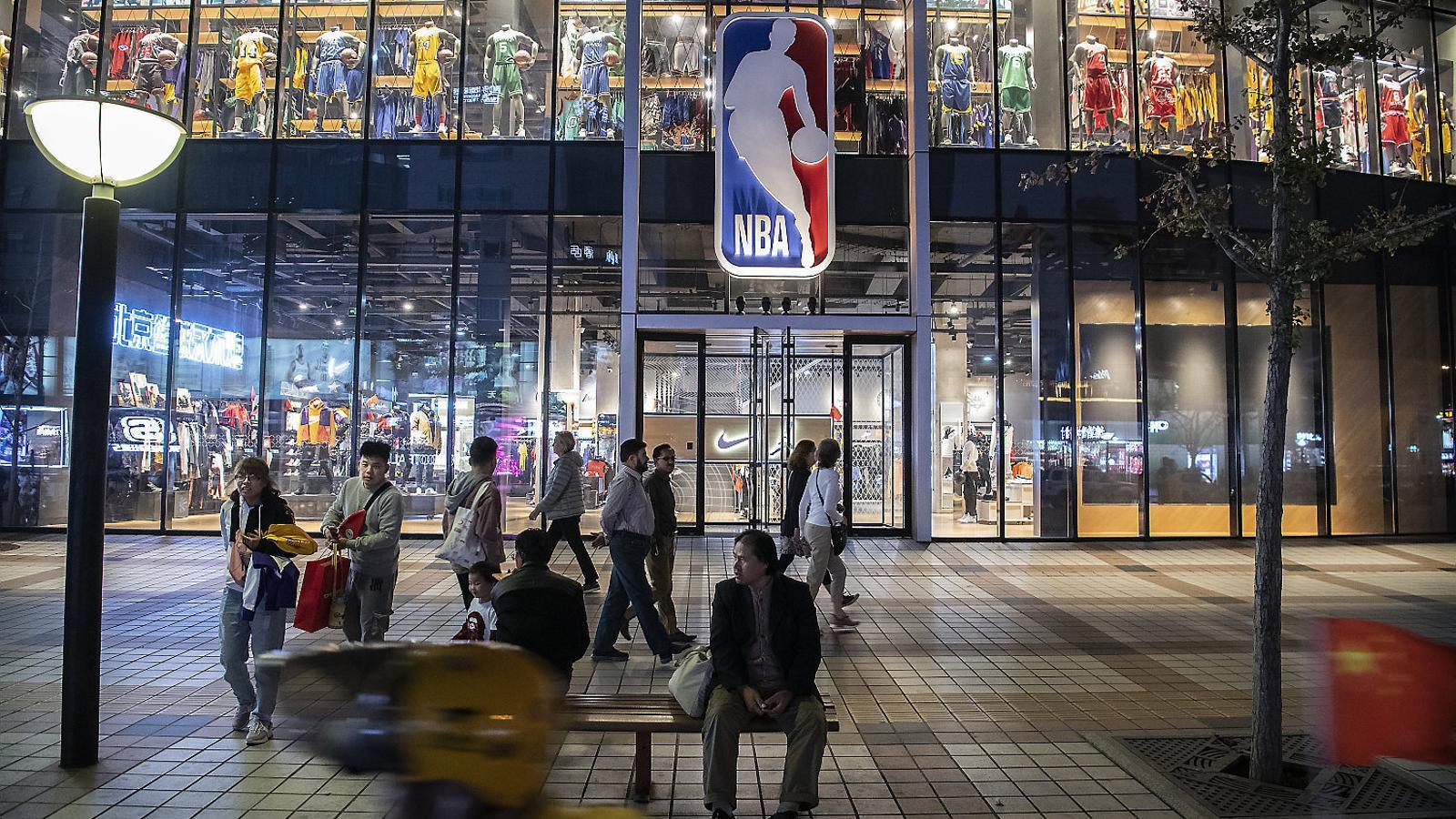Aficionats caminant prop d'una botiga de la NBA.