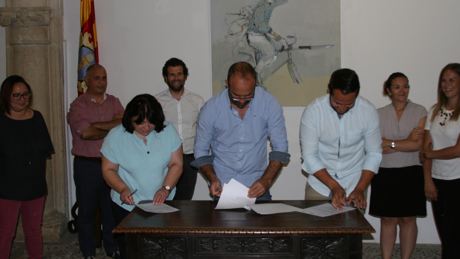 Els tres portaveus signen l'acord envoltats d'altres regidors electes.