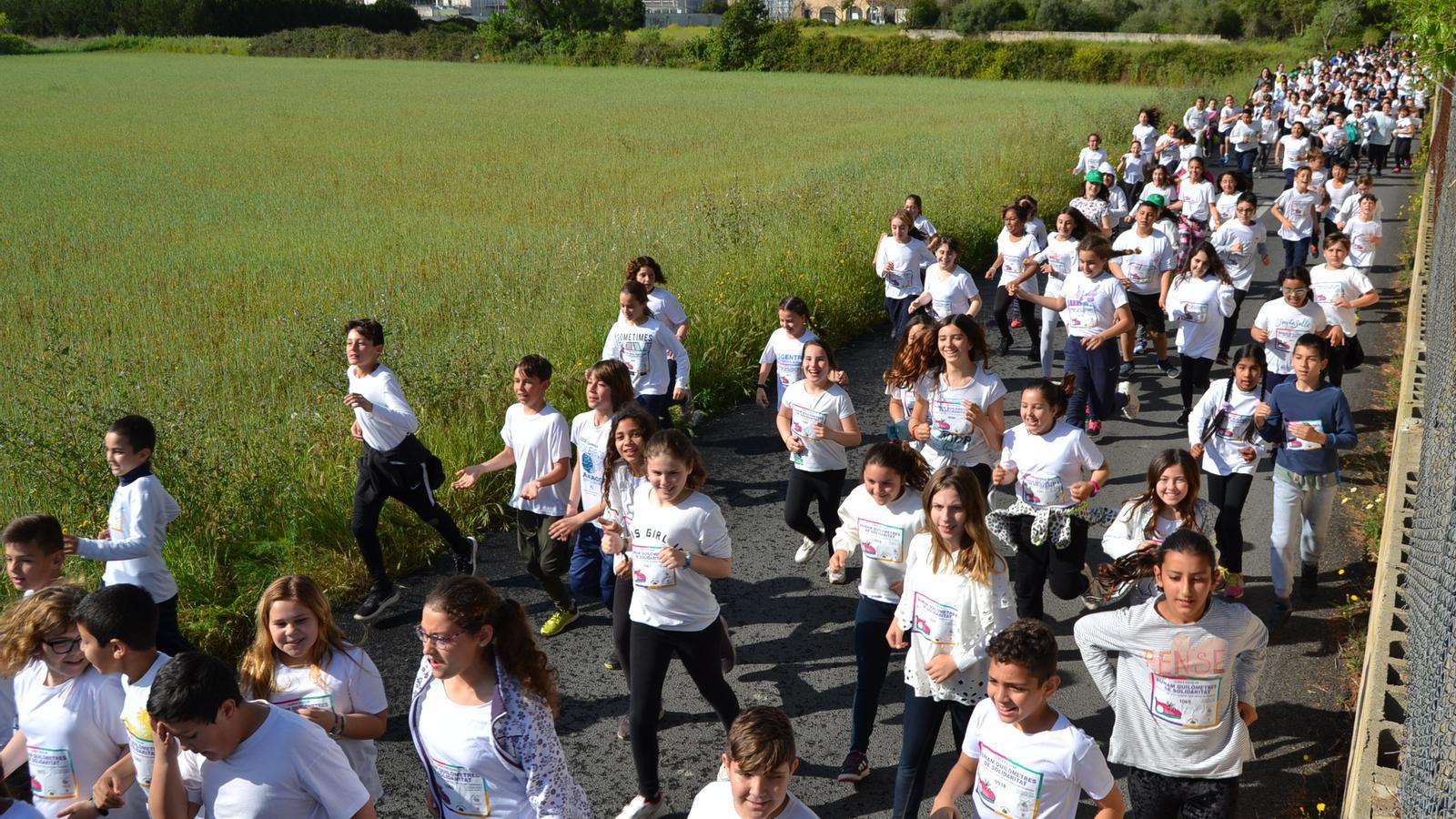Grup d'escolars corrent per la perifèria de la ciutat.