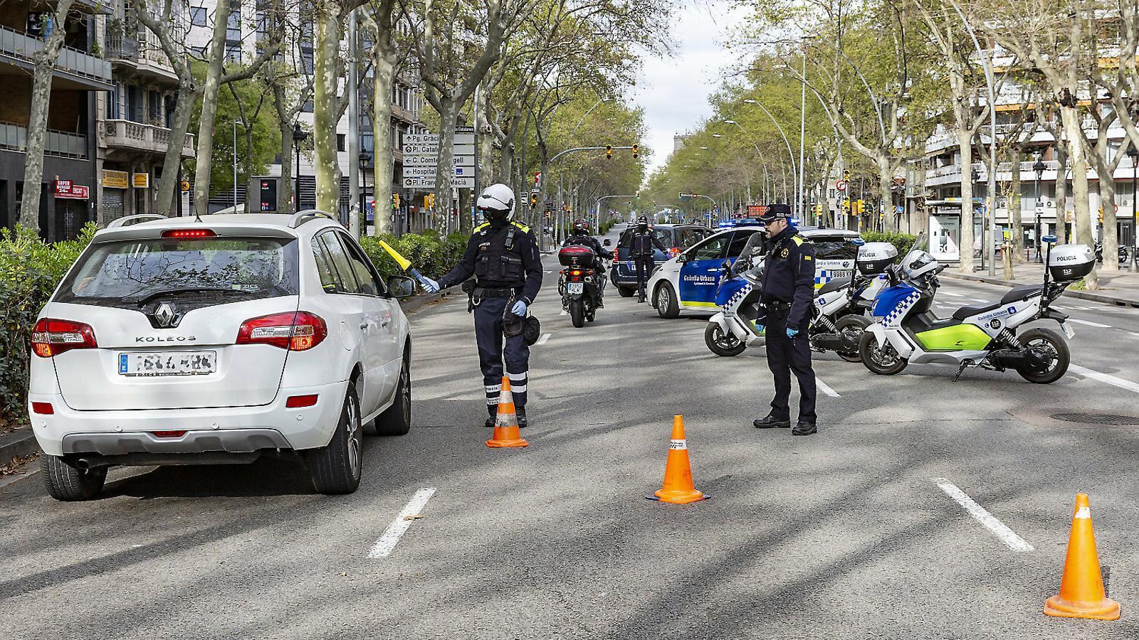 Un control de la Guàrdia Urbana a la Gran Via de Barcelona per comprovar si els conductors se salten el confinament.