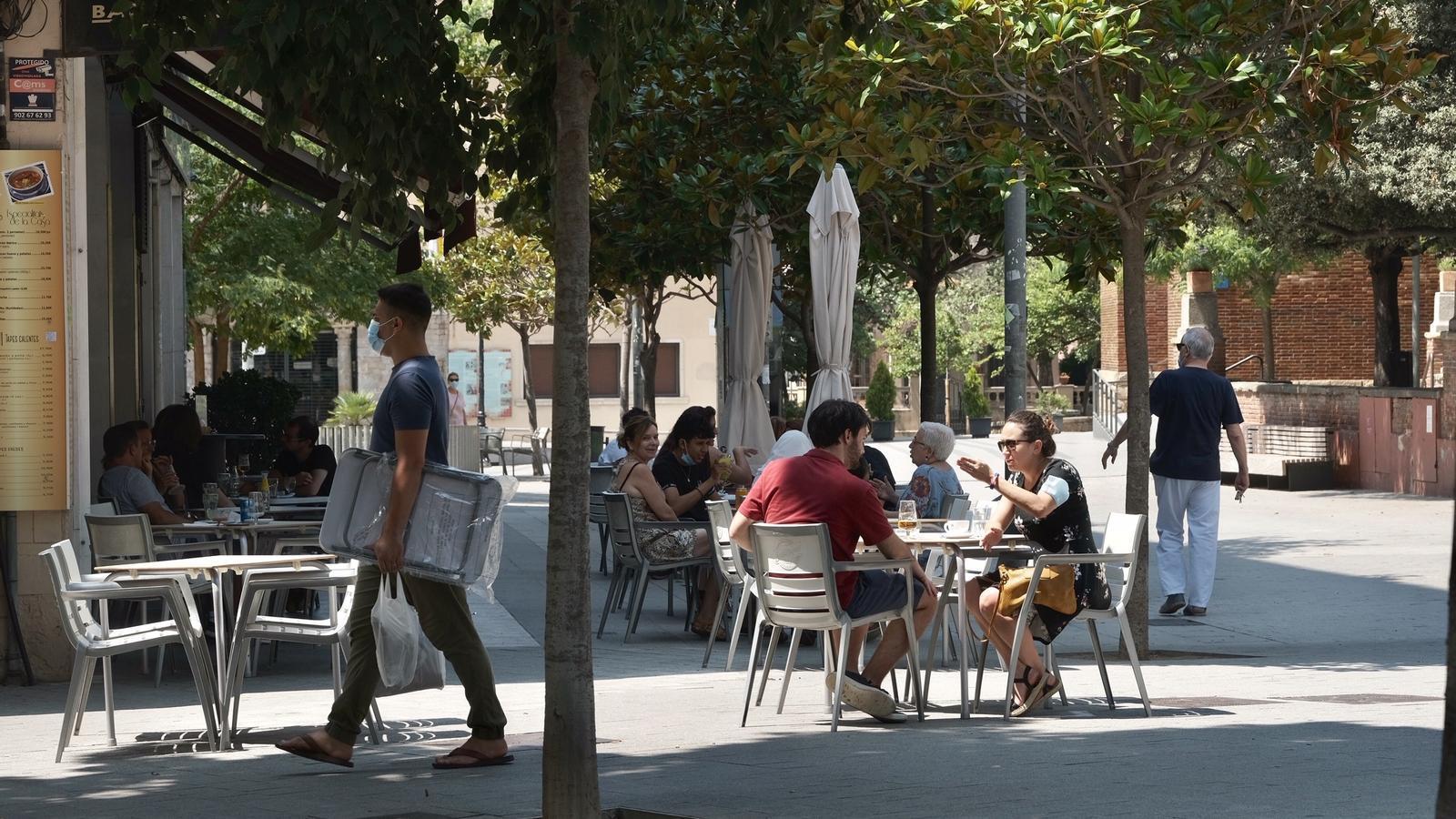 Un home amb mascareta passa per davant de la terrassa d'un bar a Cornellà de Llobregat.