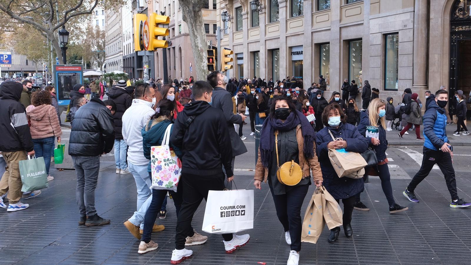 Diverses persones amb mascareta passejant i comprant aquest dimarts al centre de Barcelona.