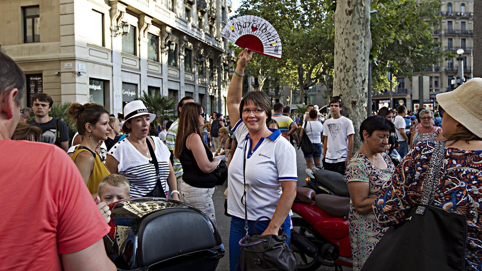 Un grup de turistes amb guia passejant-se pels carrers del centre de Barcelona.
