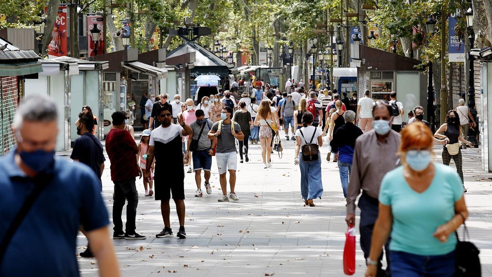 Diverses persones passejant aquest dijous per la Rambla de Barcelona.