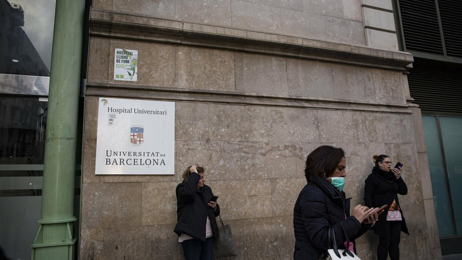 Tres dones, una de les quals protegida amb mascareta, ahir davant la porta de l'Hospital Clínic de Barcelona.