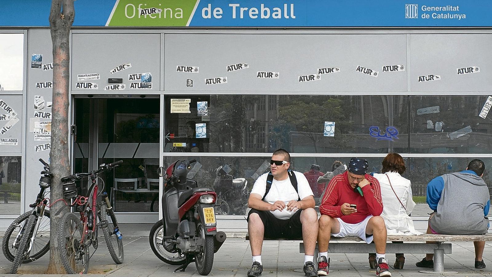 Un grup de persones fent cua a les portes de l'oficina del SOC de Badalona.