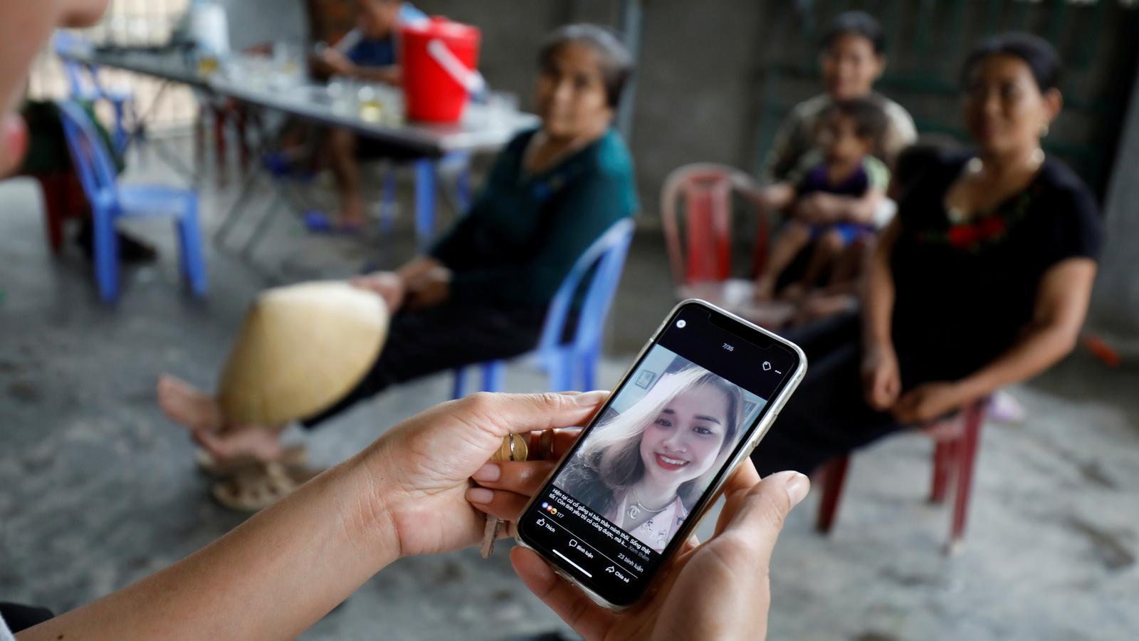 Una dona mostra la fotografia d'Anna Bui Thi Nhung, una de les suposades víctimes del camió, a la província vietnamita de Nghe An