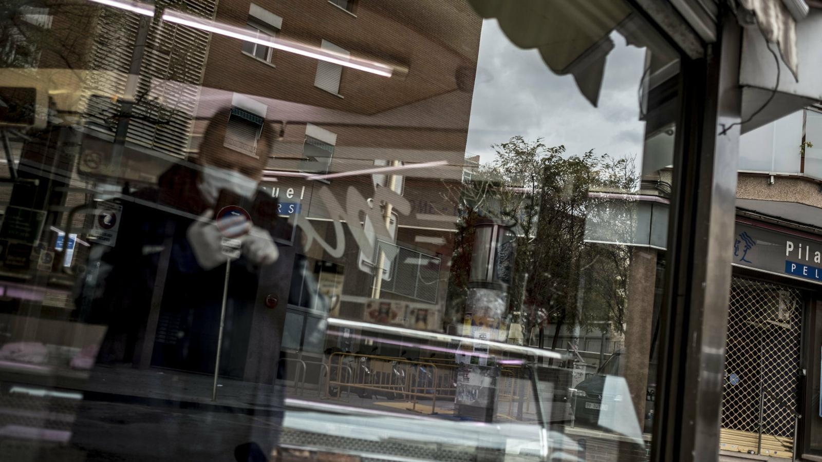 Un home dins una carnisseria de Barcelona parlant per telèfon.