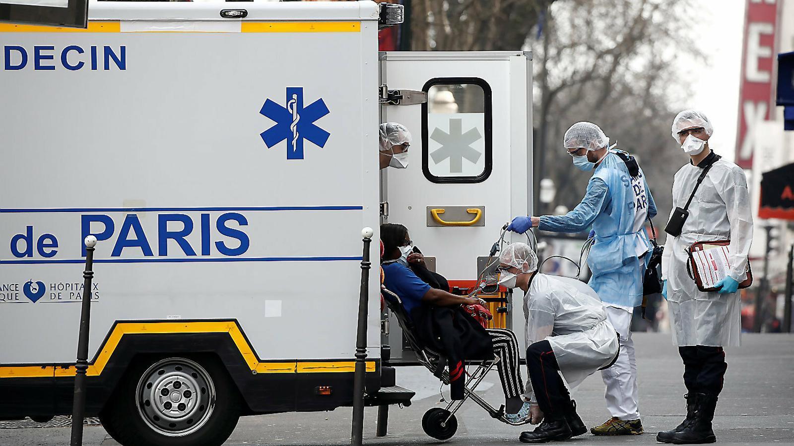 Els serveis d'emergència francesos evacuant un pacient en un carrer de París aquest divendres.
