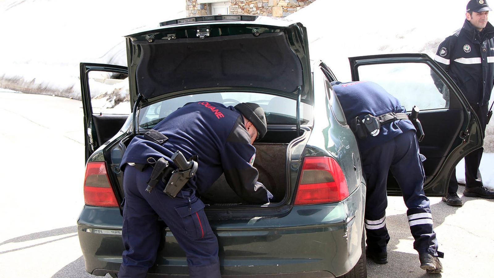 Dos gendarmes francesos inspeccionen un cotxe en presència d'un policia andorrà a la duana del Baladrà. / ARA