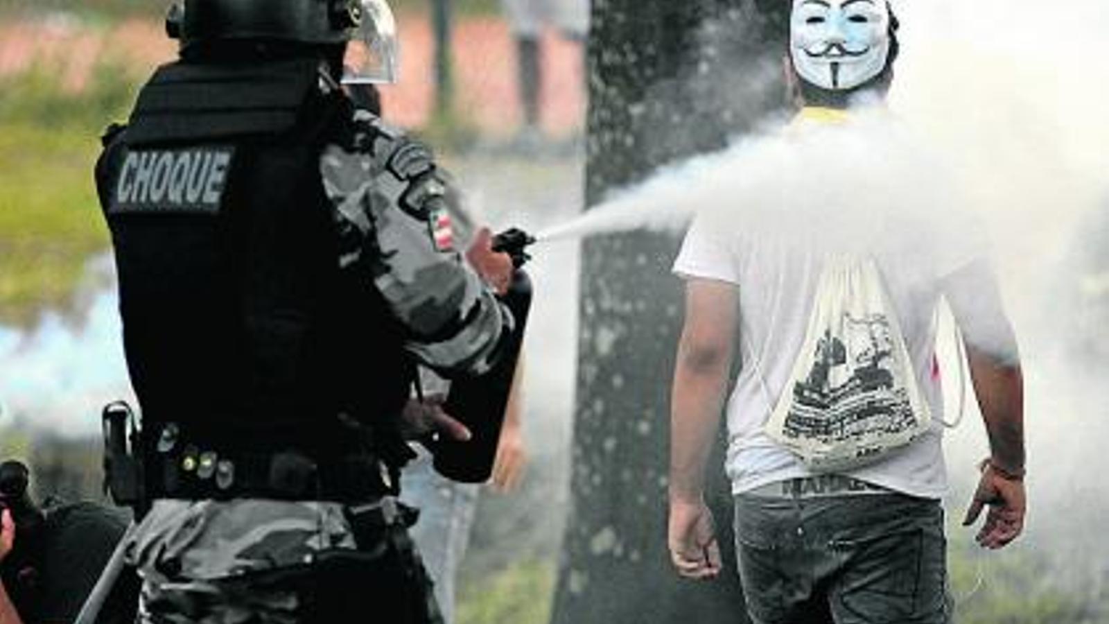 Un policia ruixant amb gas pebre un manifestant a la ciutat brasilera de Salvador el 20 de juny.
