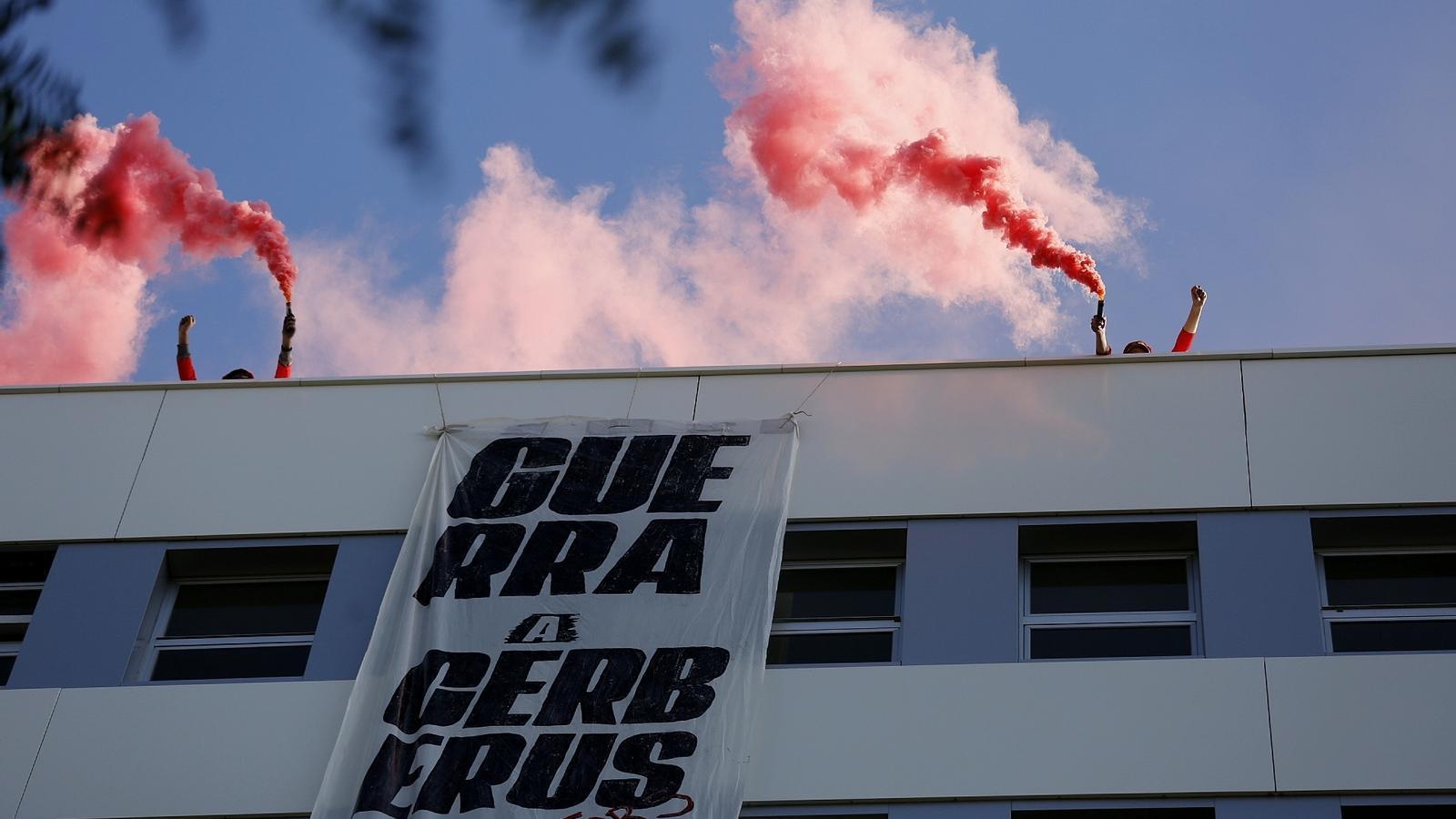 """Moment en què els activistes han pujat fins el terrat de la seu d'Haya Real State i han desplegat una pancarta amb el lema """"Guerra a Cerberus"""""""