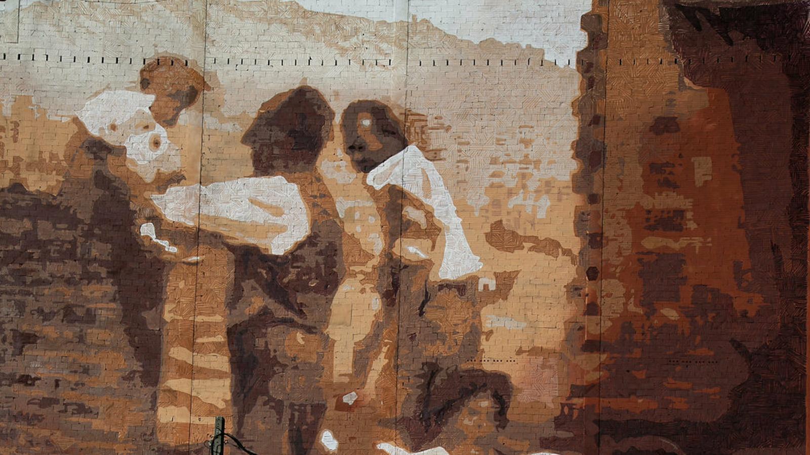Mural sobre l'autoconstrucció d'una part del barri en una mitgera de la plaça del Doctor Matias Guiu, a la Teixonera.