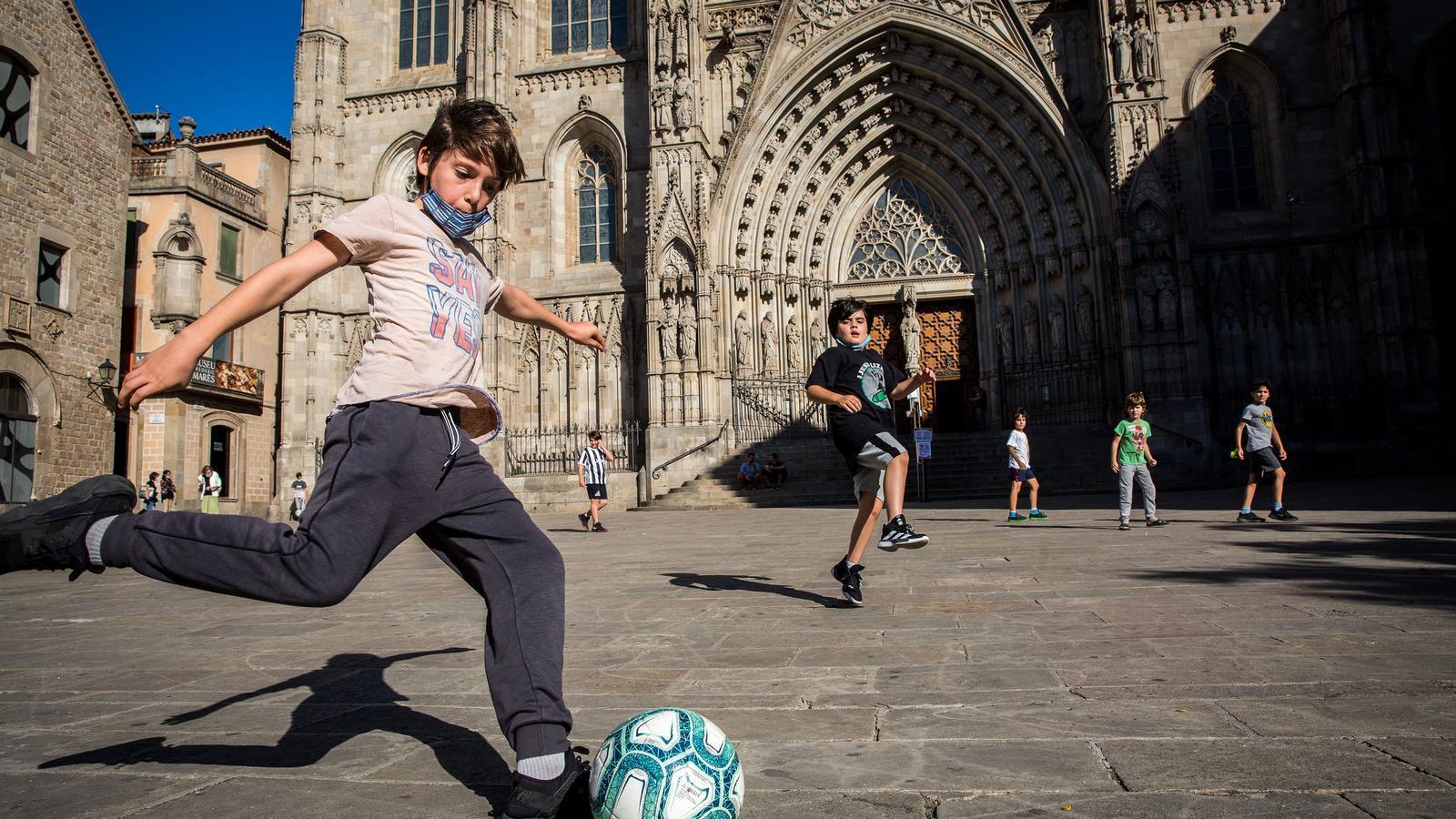 Un partit de futbol al Pla de la Seu, davant la catedral de Barcelona