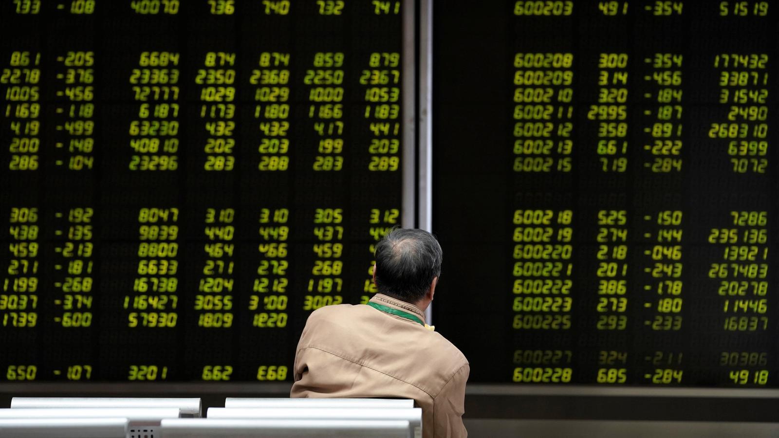 Un inversor observa les cotitzacions a les pantalles de la borsa de Pequín.