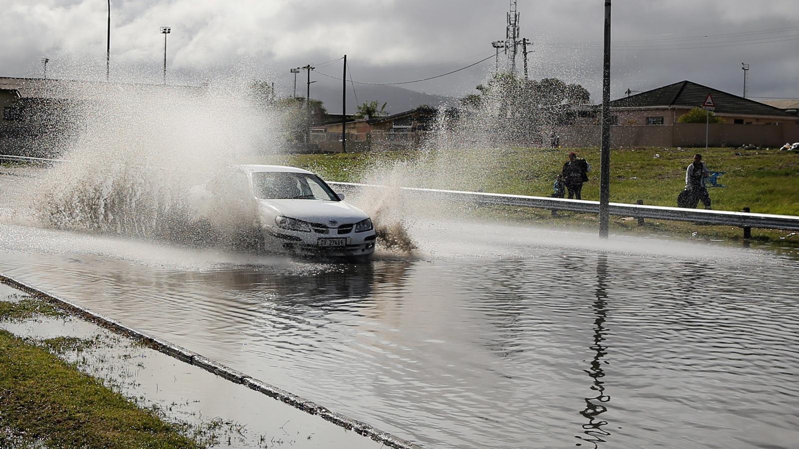 Un cotxe passa per un enorme bassal en una carretera prop de Ciutat del Cap
