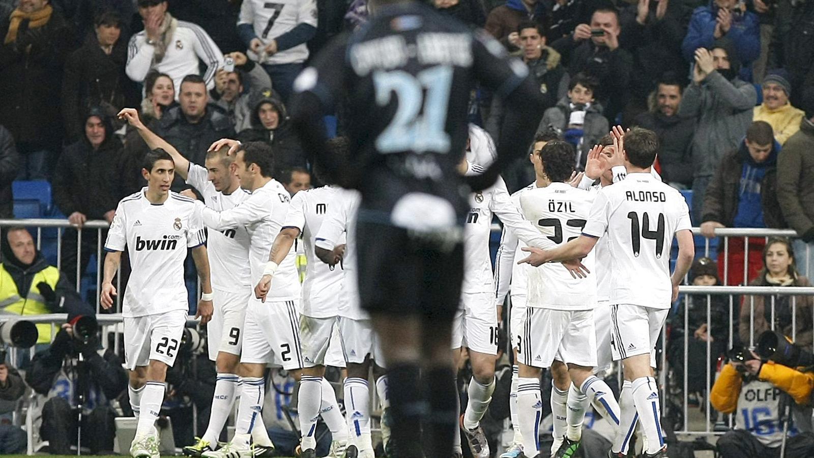 Els jugadors del Reial Madrid celebren el primer gol contra el Màlaga, obra  del davanter francès Karim Benzema. / FERNANDO ALVARADO / EFE