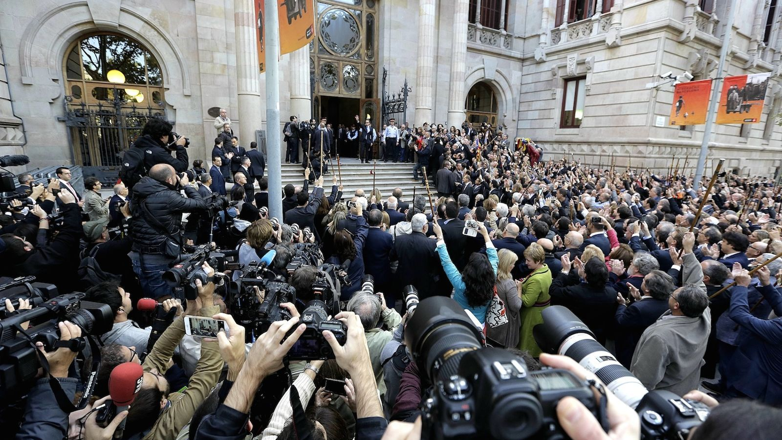 La multitud que esperava Mas davant del TSJC, ciutadans i periodistes. El president saluda des de les escales / MANOLO GARCÍA
