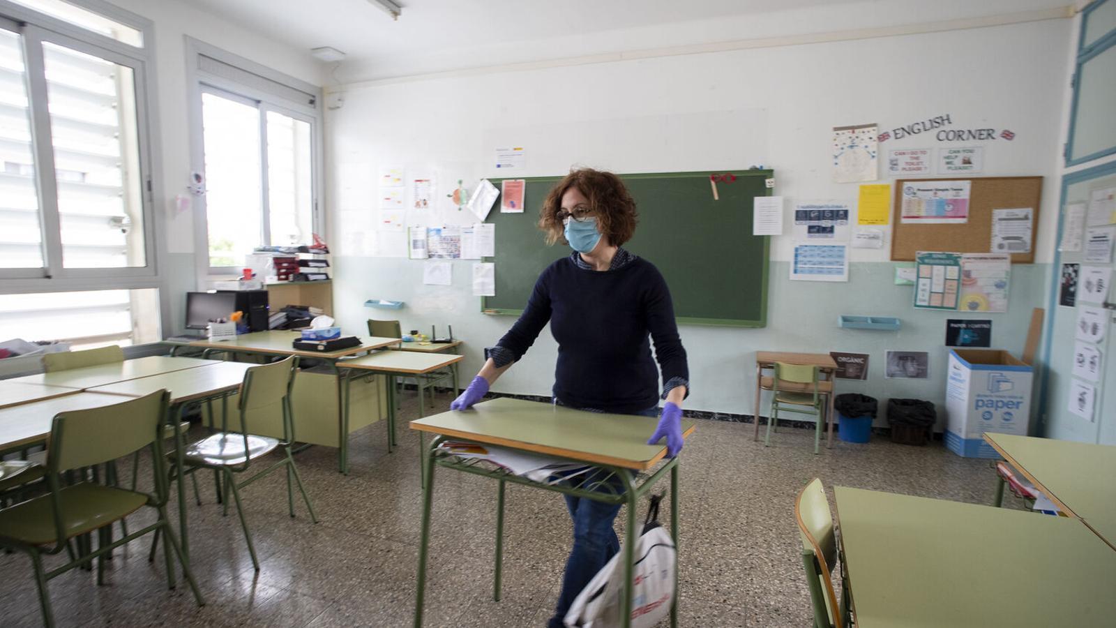 Una mestra reorganitza les taules d'una classe, en una imatge d'arxiu.