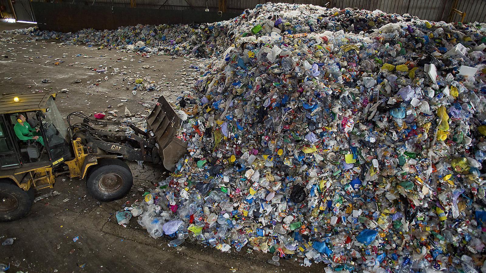 Un operari apilant les muntanyes de plàstic que entren a la planta de triatge de Gavà, que   dona servei als municipis de l'Àrea Metropolitana de Barcelona.
