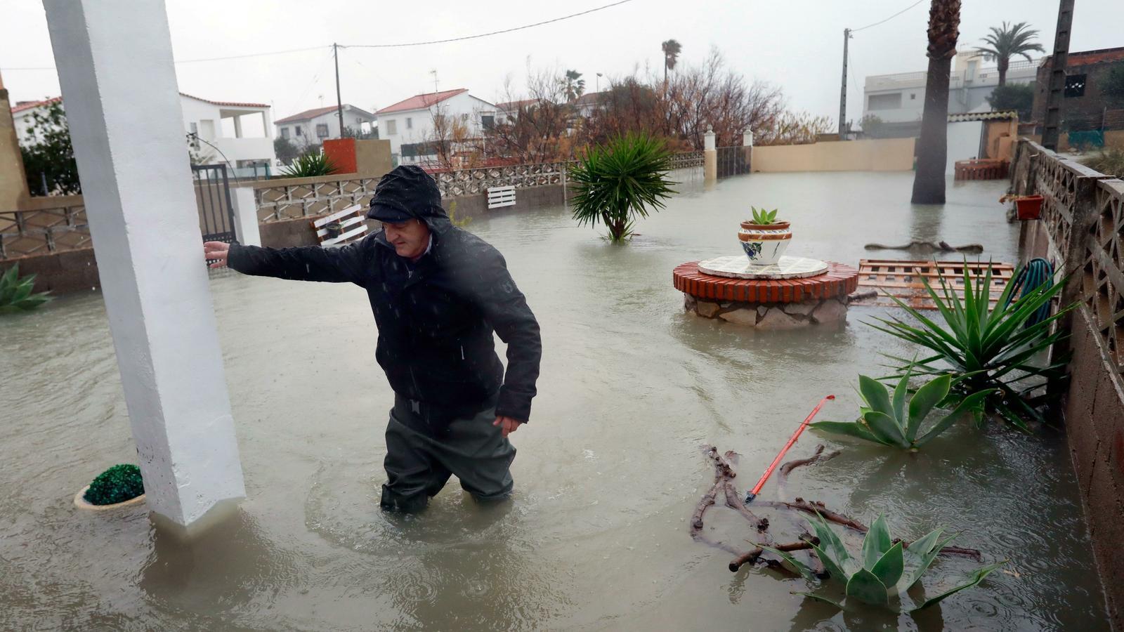 Un veí intenta entrar a casa seva a Almenara, a Castelló, lluitant contra el temporal