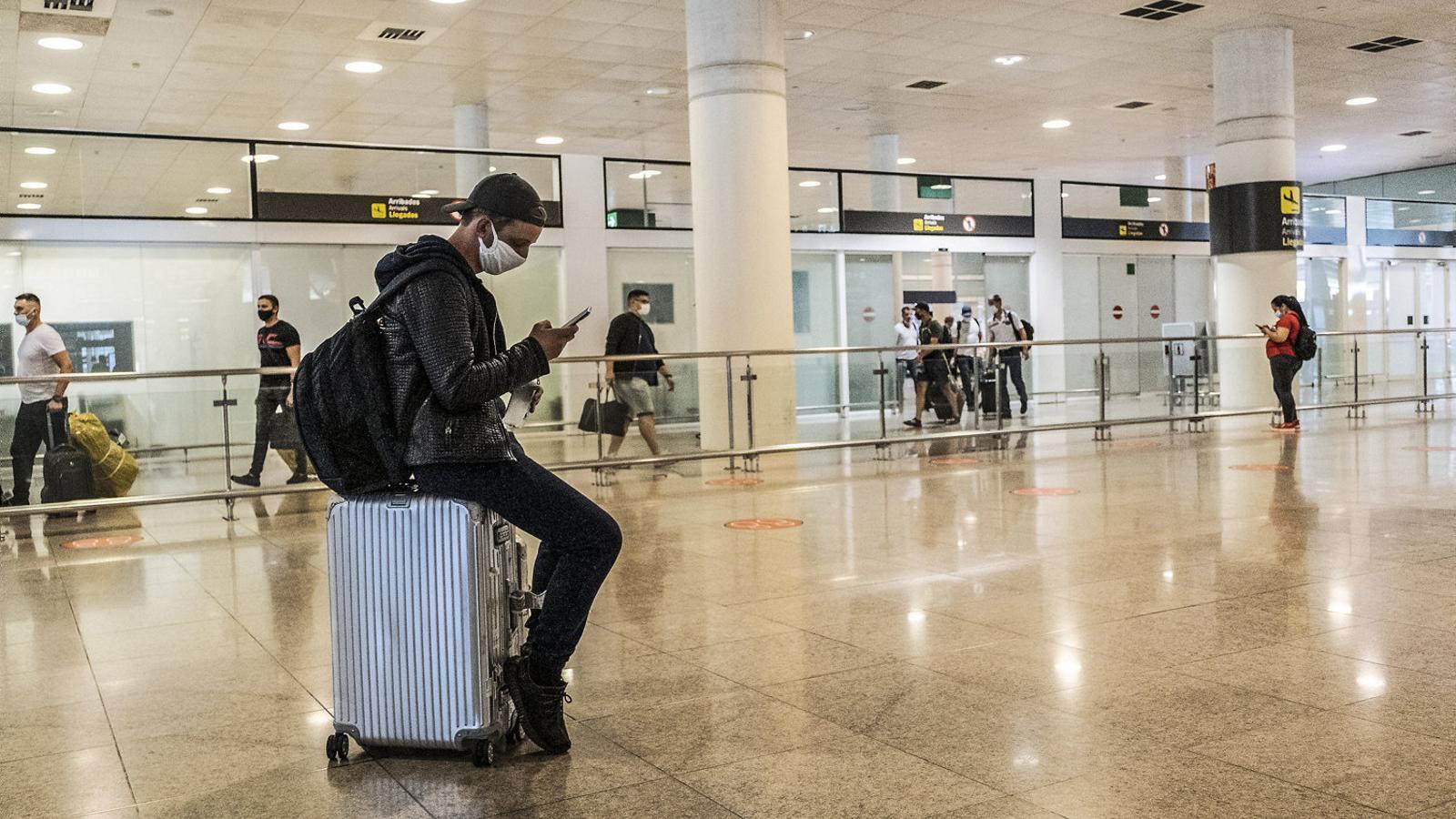 Un passatger esperant a l'aeroport del Prat després del confinament dur.