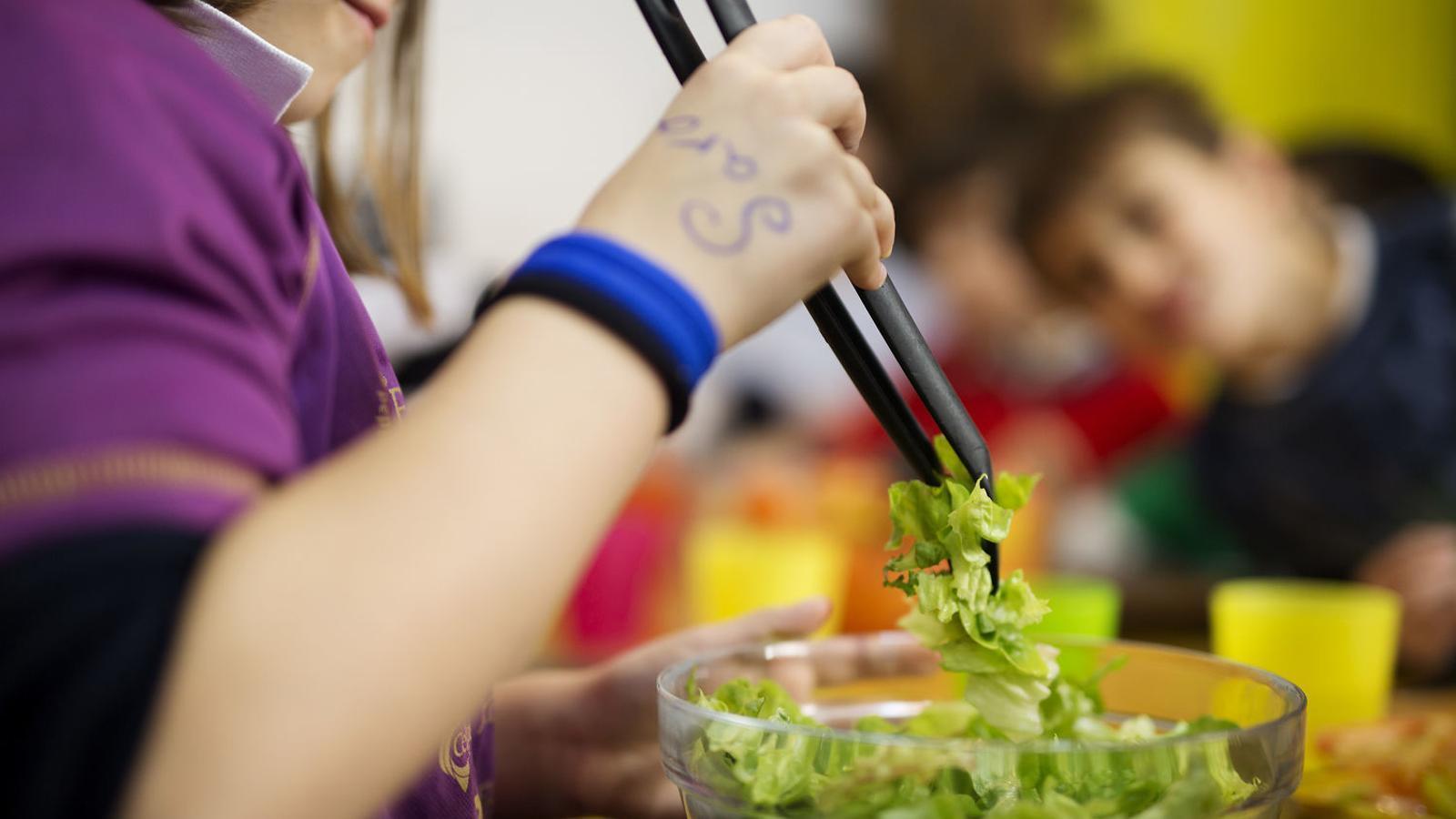 Una nena es serveix un plat d'amanida al menjador de la seva escola