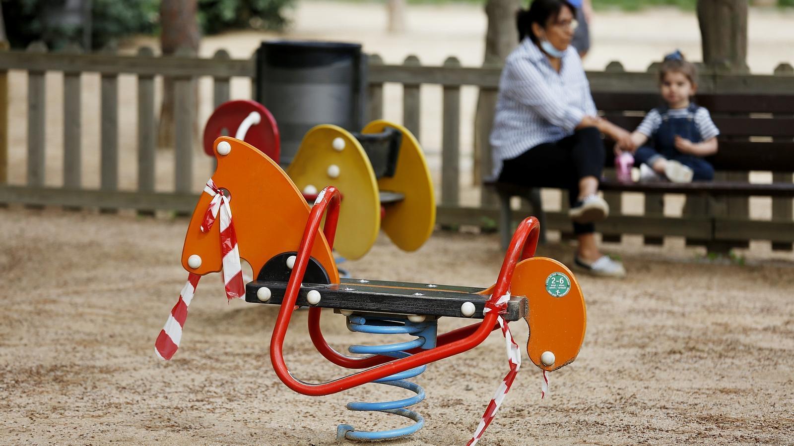Una dona i una nena dins del recinte infantil tancat al parc Joan Miró